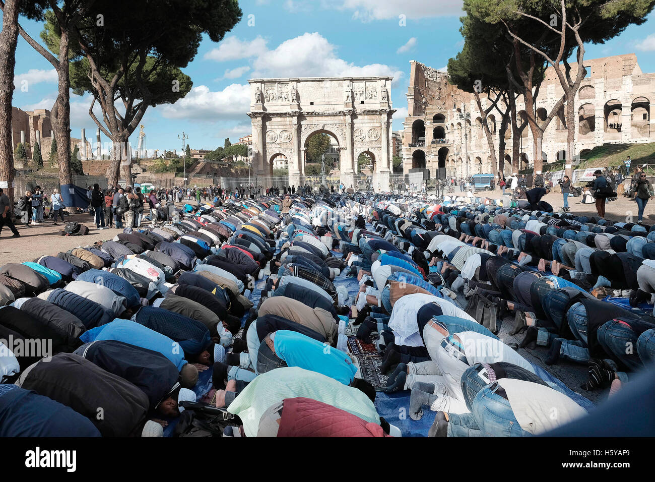 Rome, Italy. 21st Oct, 2016.  Muslims pray in front of the Colosseum and the Arch of Constantine, to protest against - Stock Image