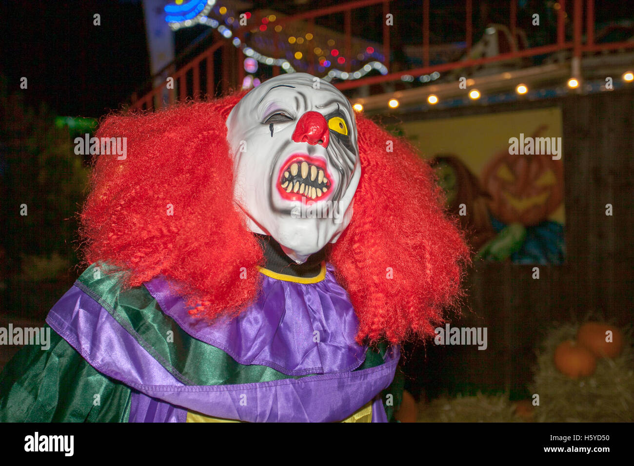 A killer Halloween clown with mask, white face, red hair wig
