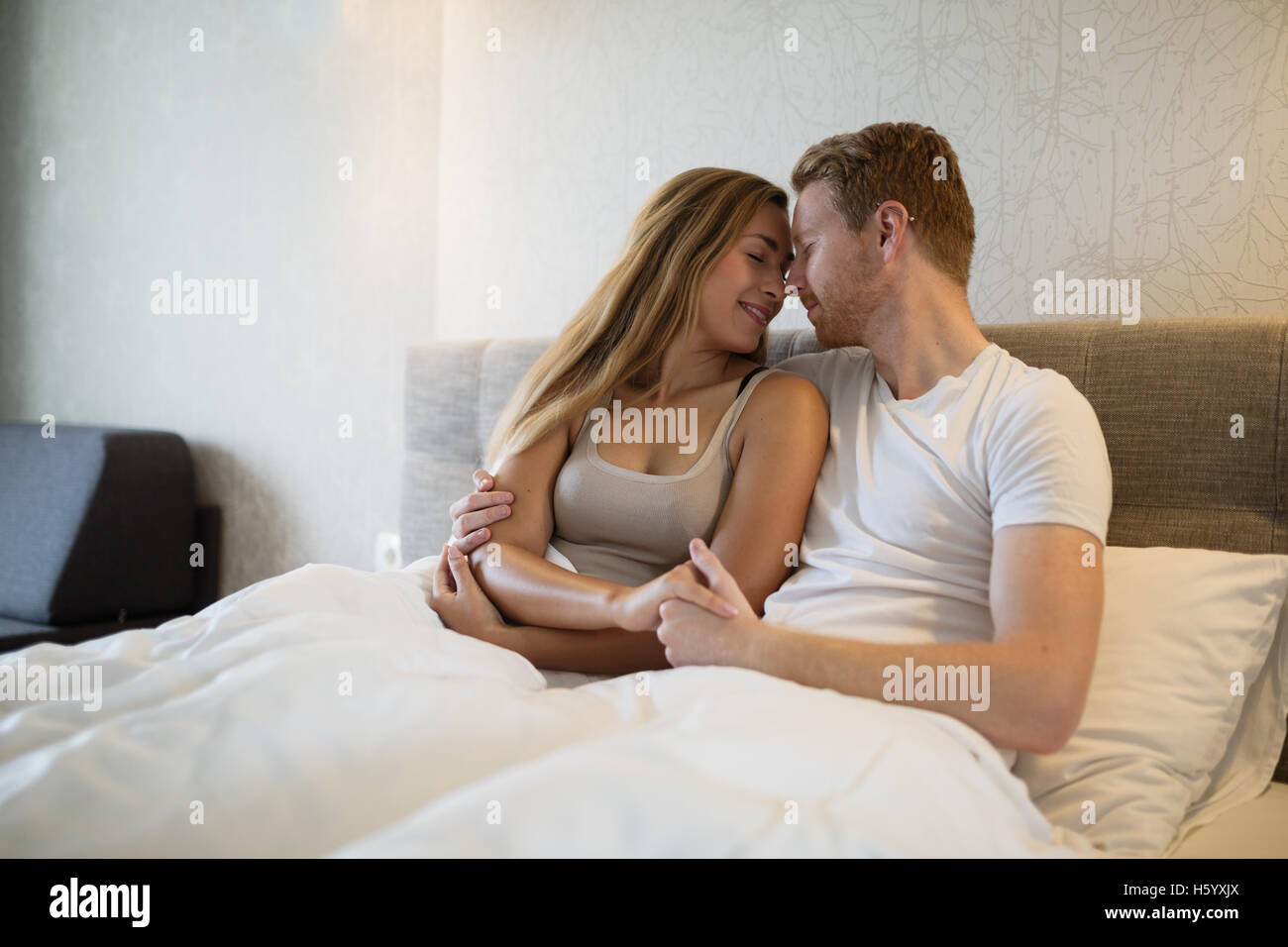 Romantic relaxed couple hugging in bed Stock Photo