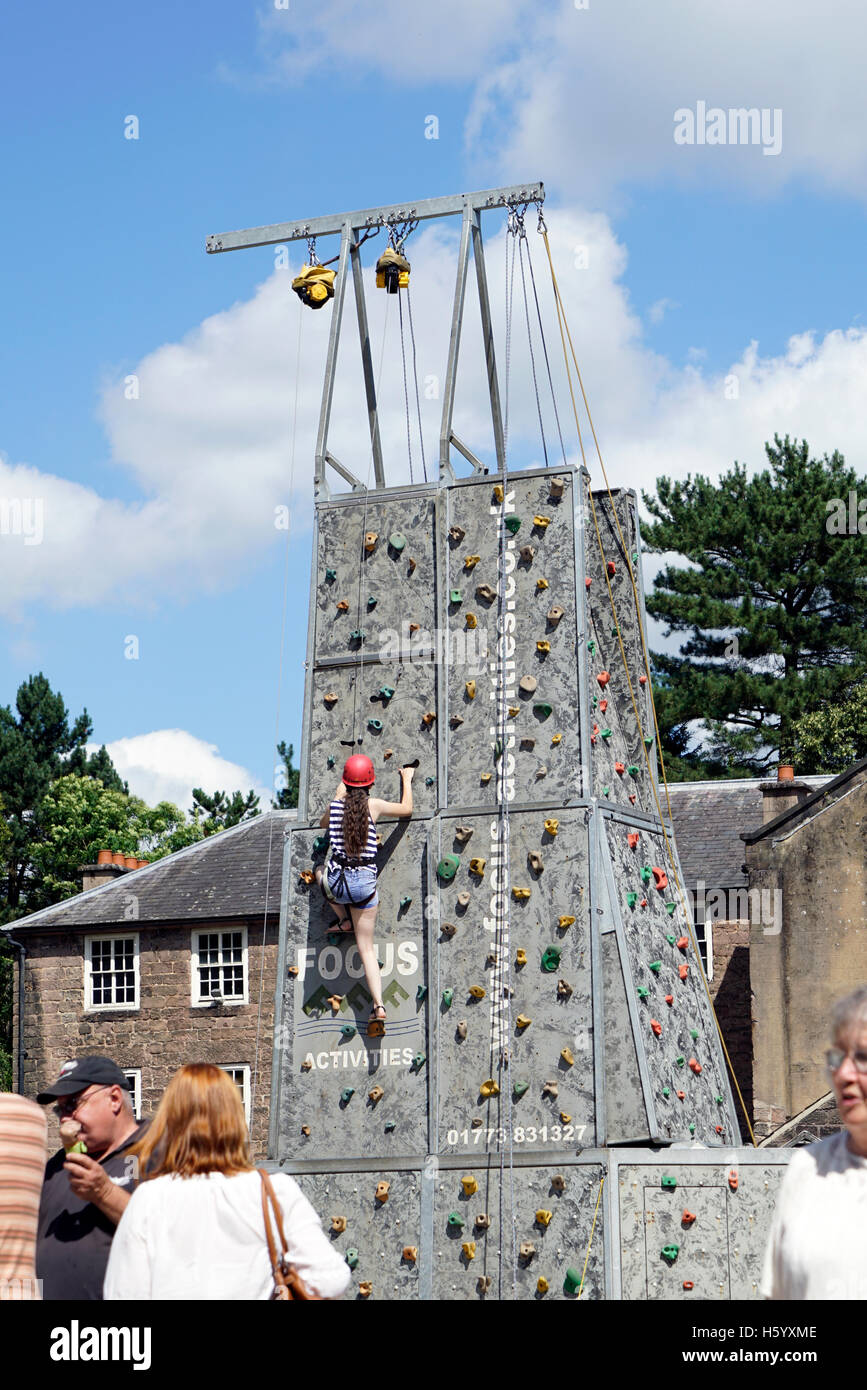 Child /girl climbing mobile  rock tower at event Derbyshire England - Stock Image