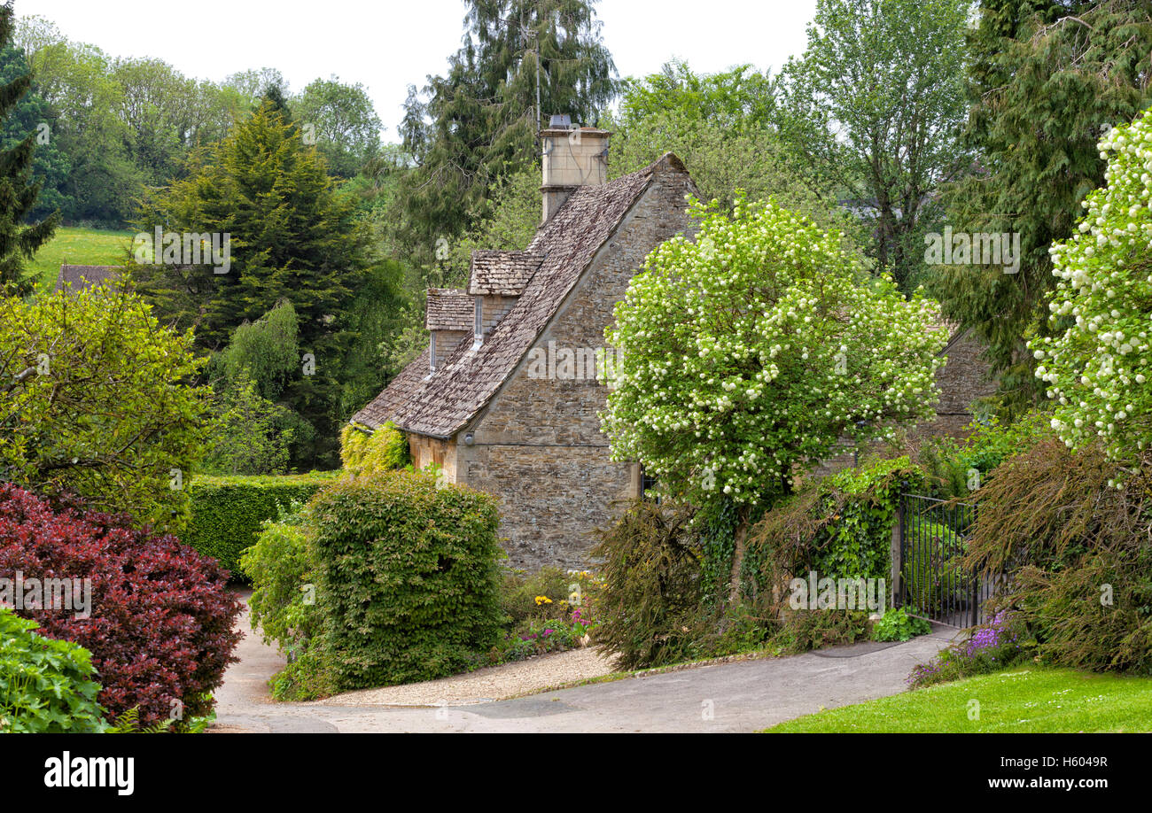 Traditional old stone house surrounded by trees, shrubs and flowers in rural English countryside village - Stock Image