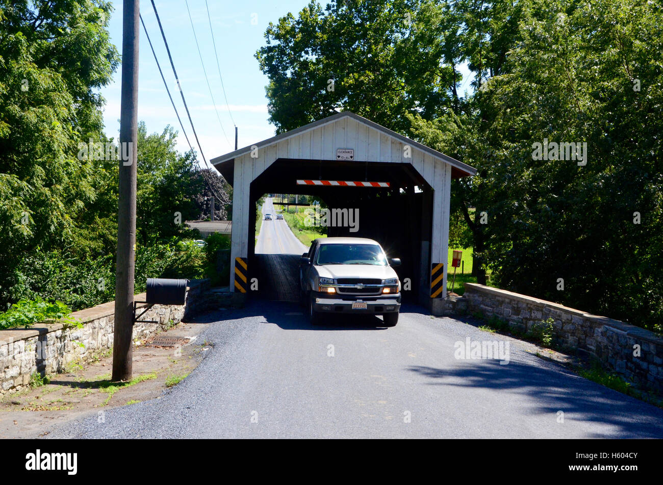 covered wooden bridge pennsylvania with car passing through on sunny day with trees and postal box on lamp post - Stock Image