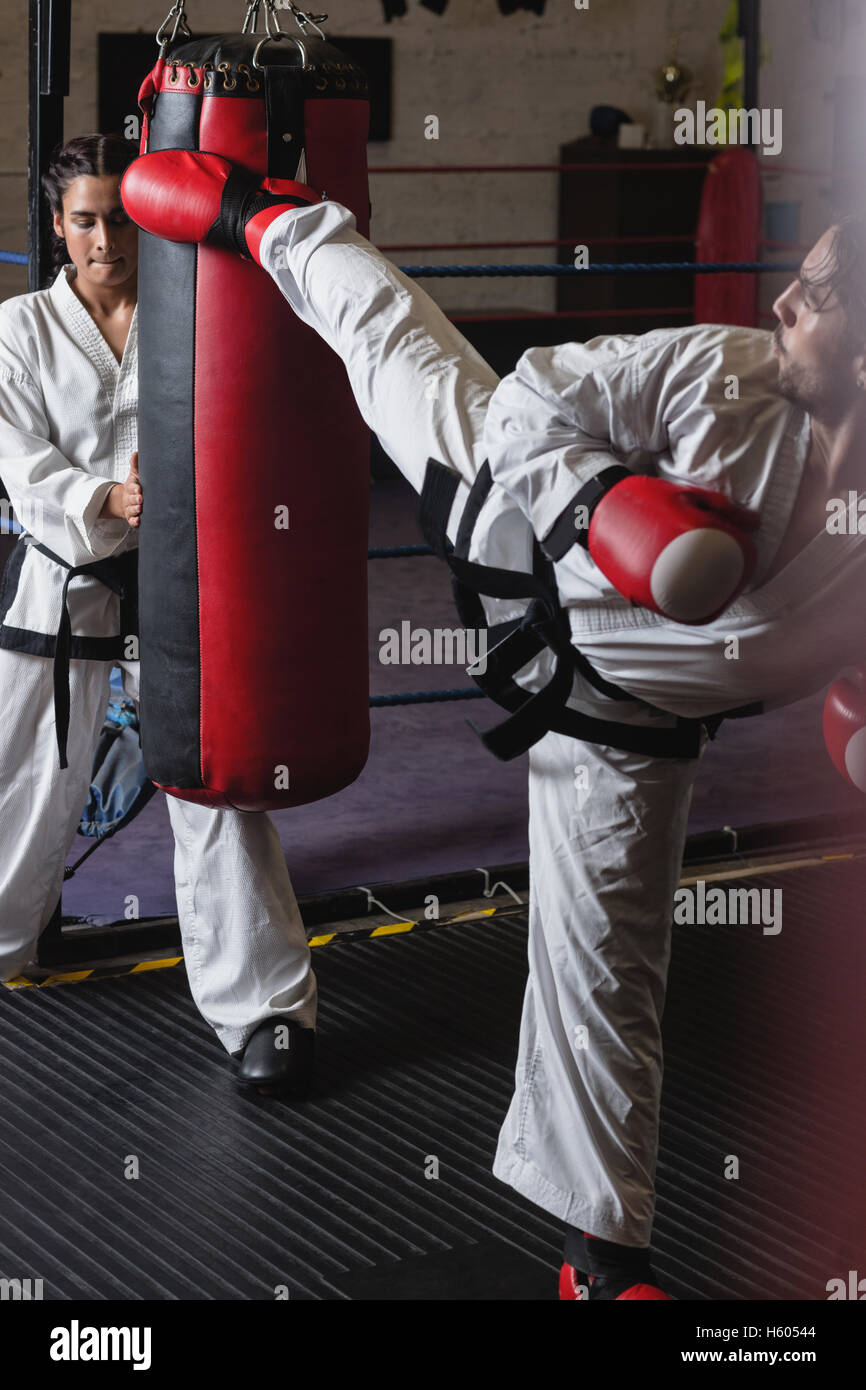 Man and woman practicing karate with punching bag - Stock Image