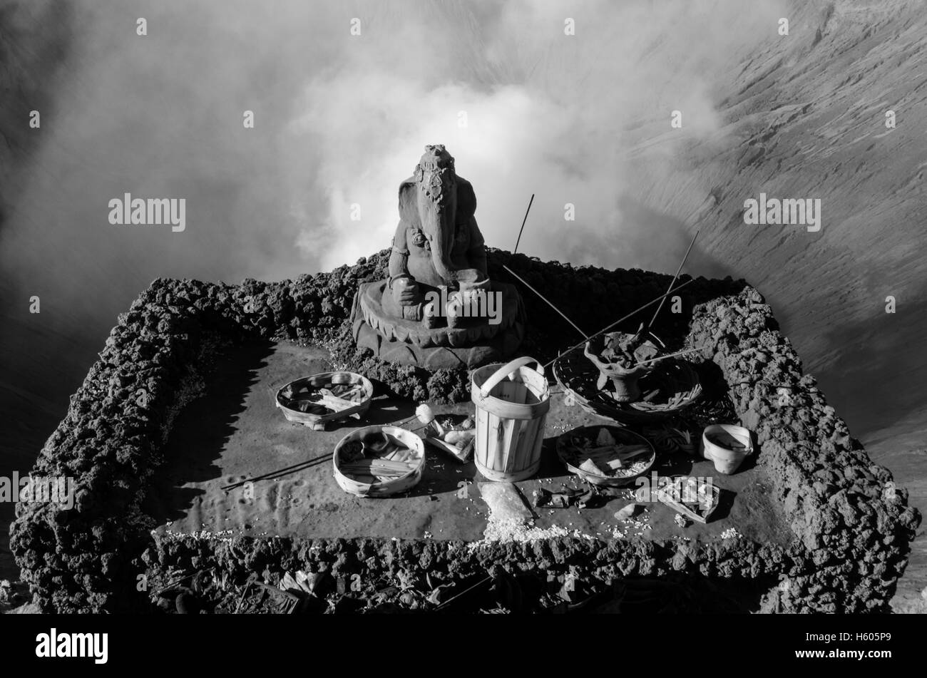 A religious shrine above the smoking volcano crater of Mount Bromo - Stock Image