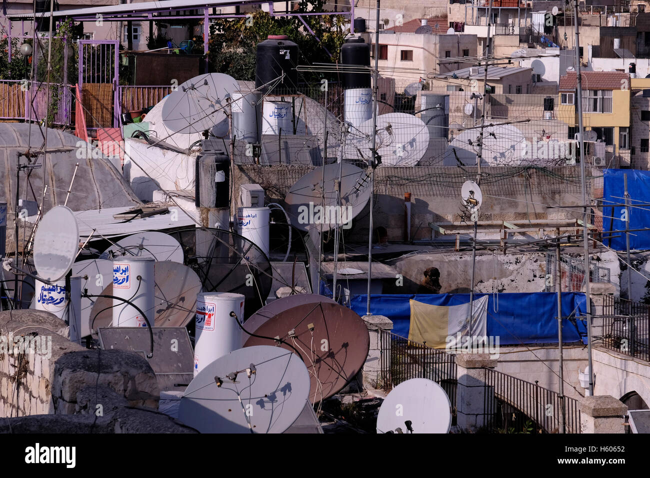 White tanks of water-heaters and satellite dishes on rooftop of houses at the Muslim Quarter Old city East Jerusalem - Stock Image