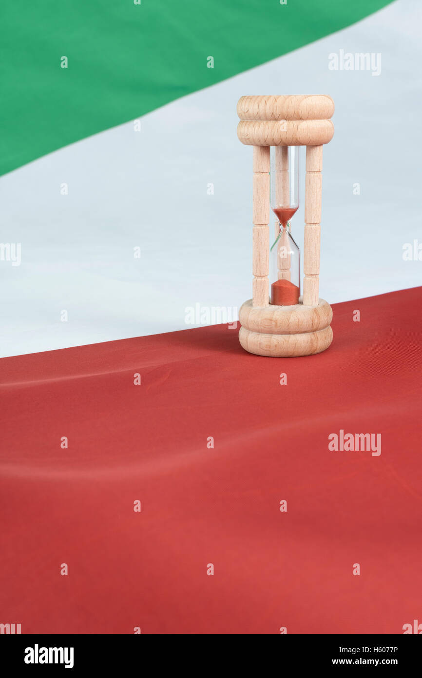 Wooden egg timer set against an Italian flag - a visual metaphor for time running out for Italian banks and financial - Stock Image
