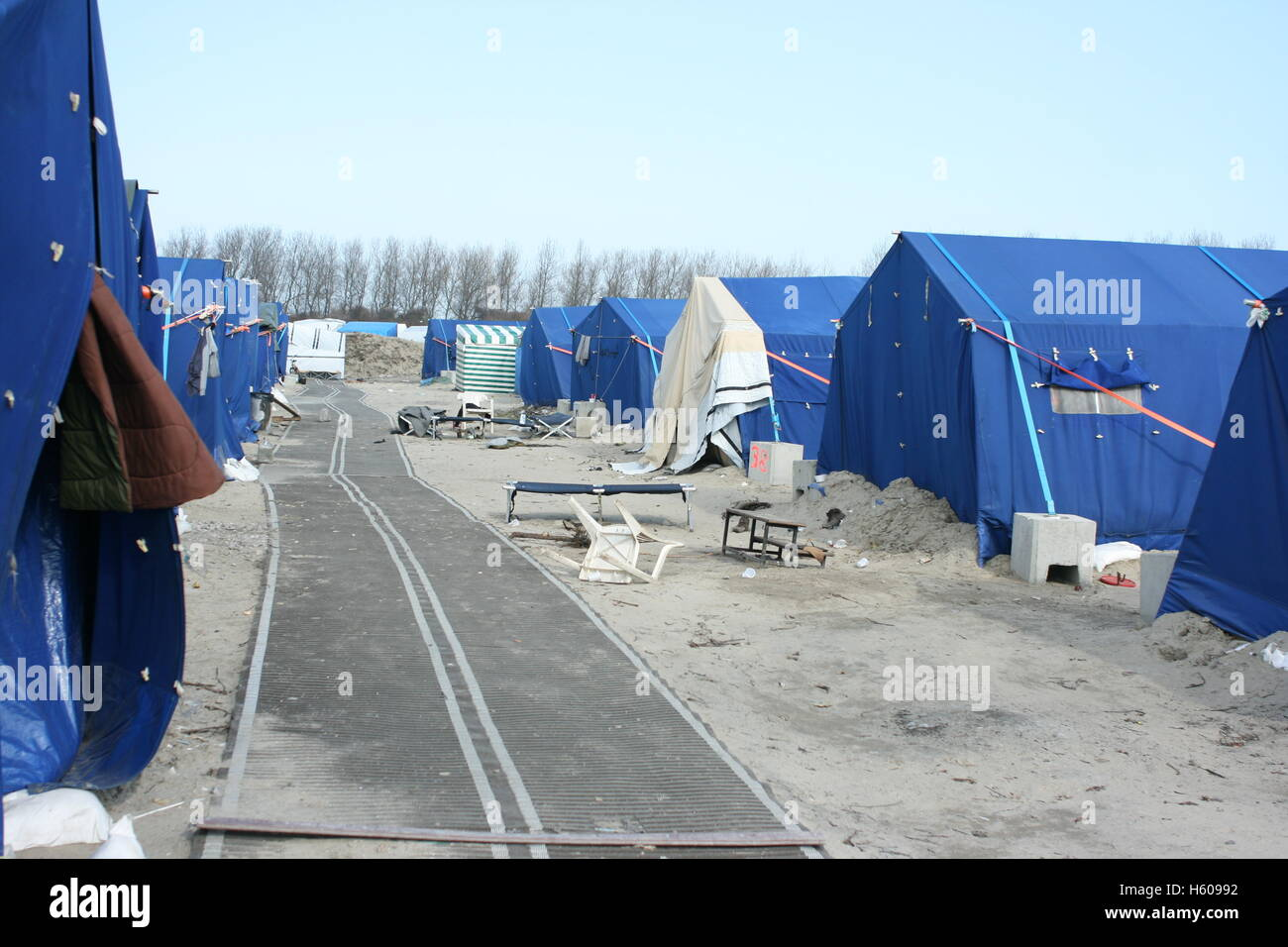 Blue tents are set up by aid organisations to give the residents of Calais refugee camp a more secure, warm and - Stock Image