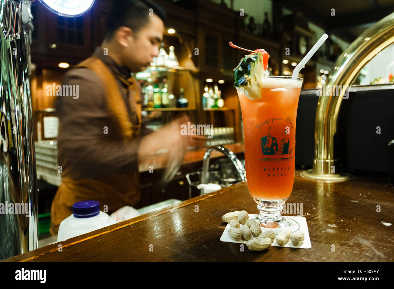 A barman mixes a Singapore Sling in the Long Bar, Raffles hotel, Singapore - Stock Image