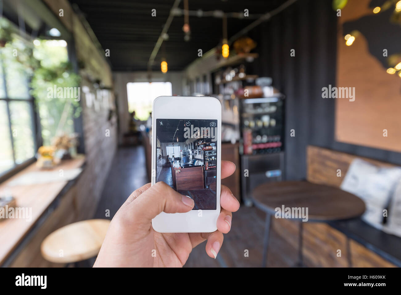 People using smartphone take a photo in coffee shop. Coffee shop is a most popular place to check in and take a - Stock Image