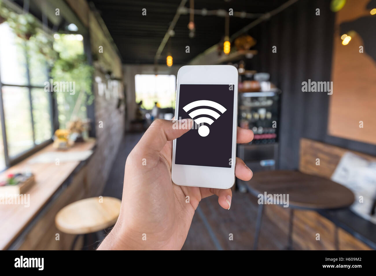 Hand using Smart phone in coffee shop. in coffee shop have free wifi for customer be can using connect social network - Stock Image
