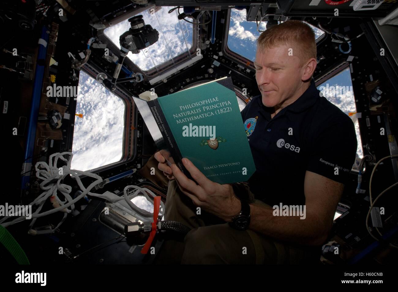 NASA International Space Station Expedition 46 British astronaut Tim Peake reads Principe Mathematica by Isaac Newton - Stock Image