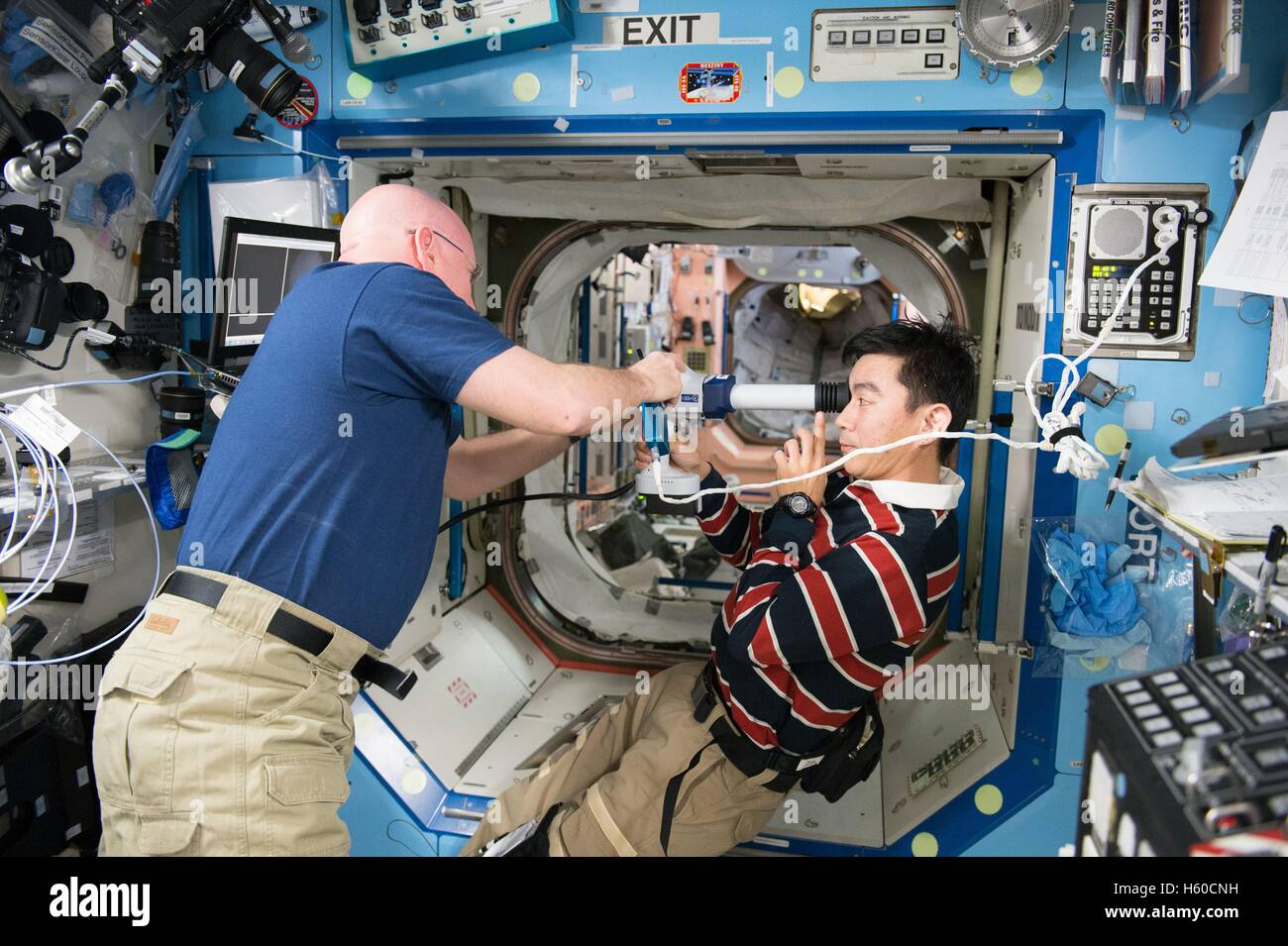 NASA International Space Station Expedition 44 mission astronaut Scott Kelly assists Japanese astronaut Kimiya Yui - Stock Image