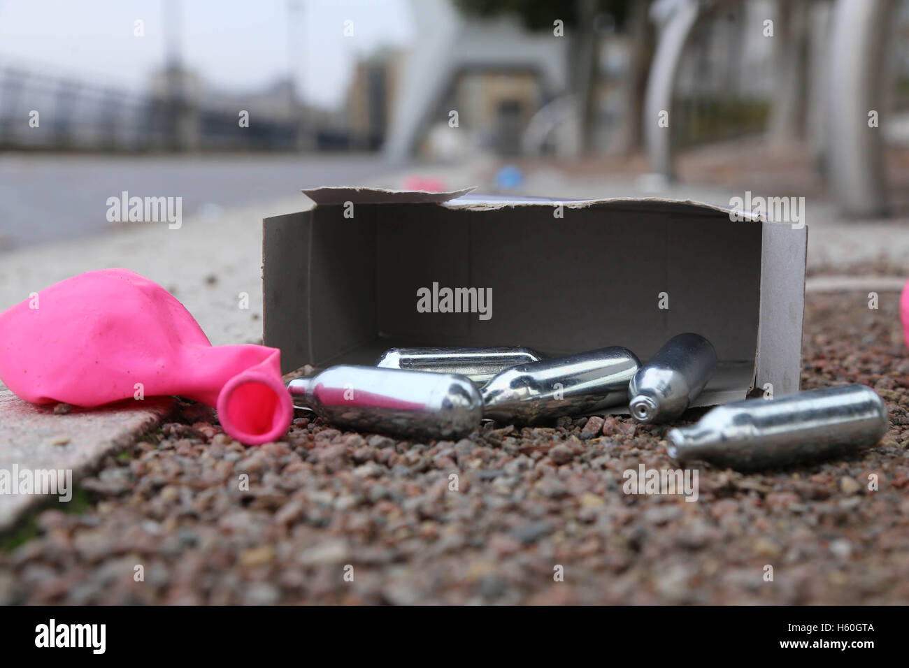 Nitrous Oxide canisters, balloons and boxes litter the Thames Path after youths spend the night inhaling the  laughing - Stock Image