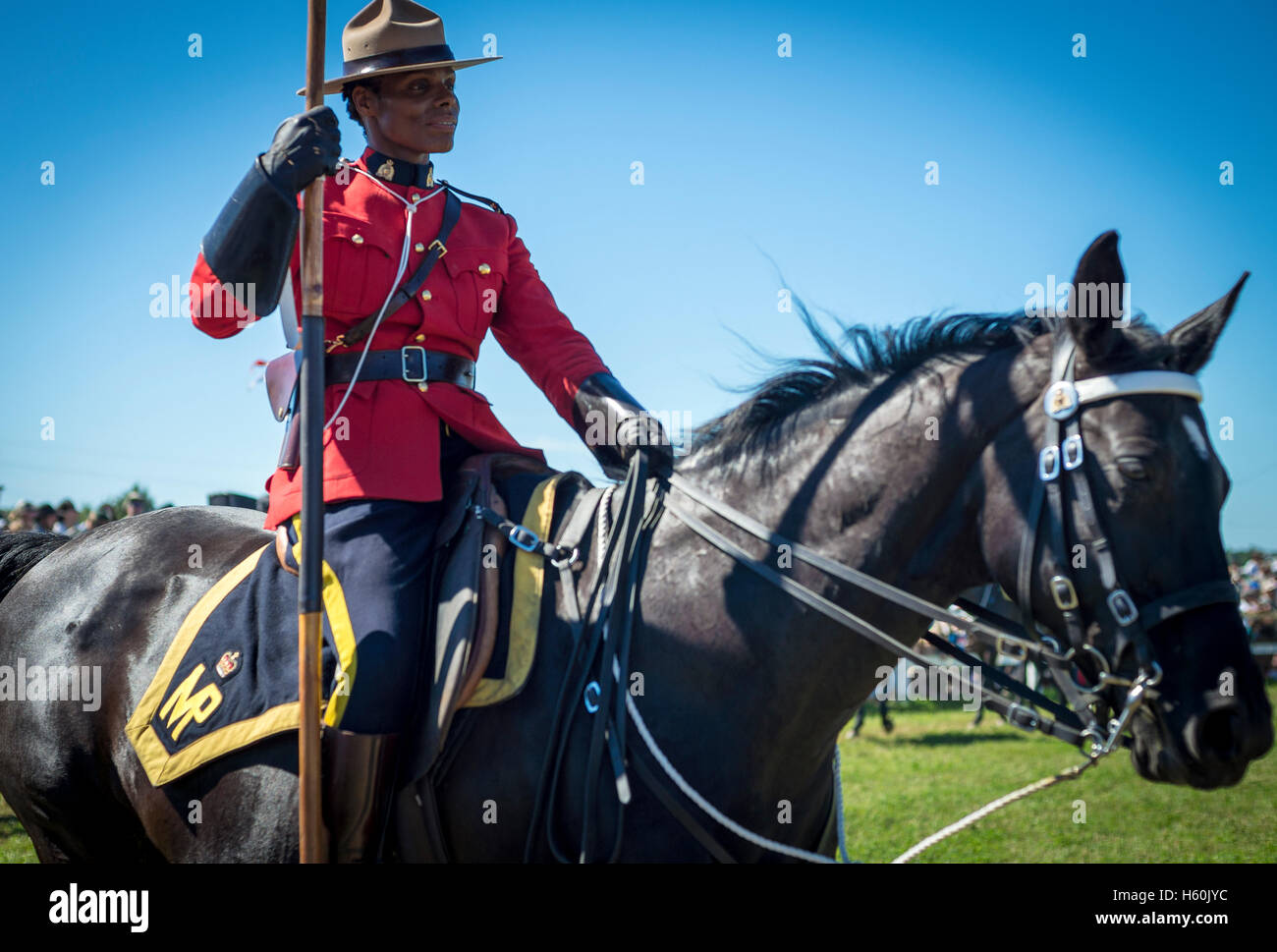 Female RCMP Mountie riding a horse during a musical ride ceremony - Stock Image