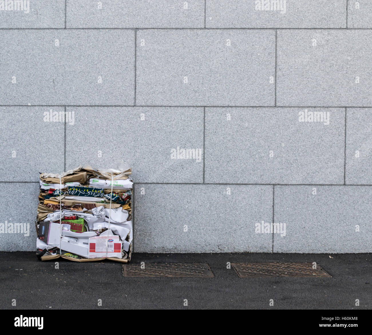 Flattened paper and cardboard recycling sits against a grey stone wall with drain covers on the path - Stock Image