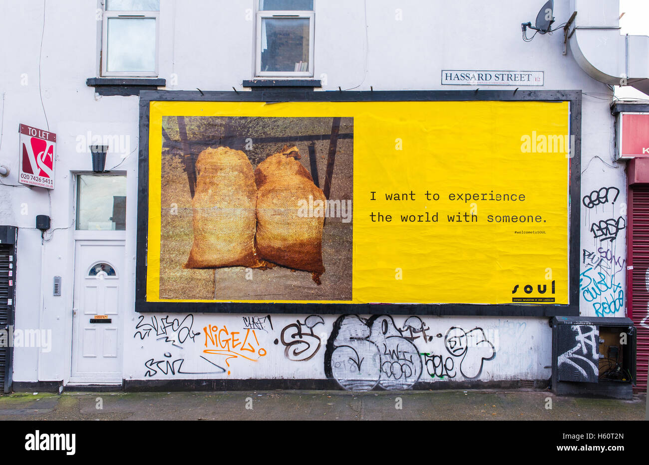 Big yellow billboard with words 'I want to experience the world with someone' fixed on a white wall on the - Stock Image