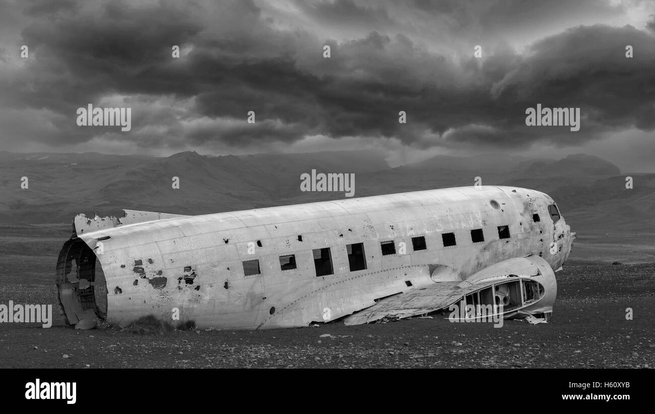 The abandoned wreck of a US military plane on Solheimasandur beach near Vik, Southern Iceland - Stormy clouds - Stock Image