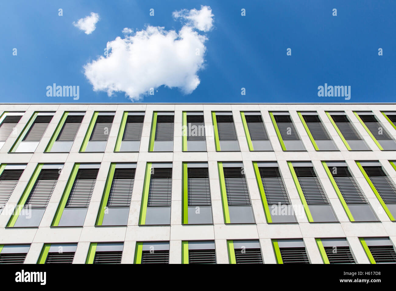 facade of a modern office building, small windows, blue sky cloud, - Stock Image