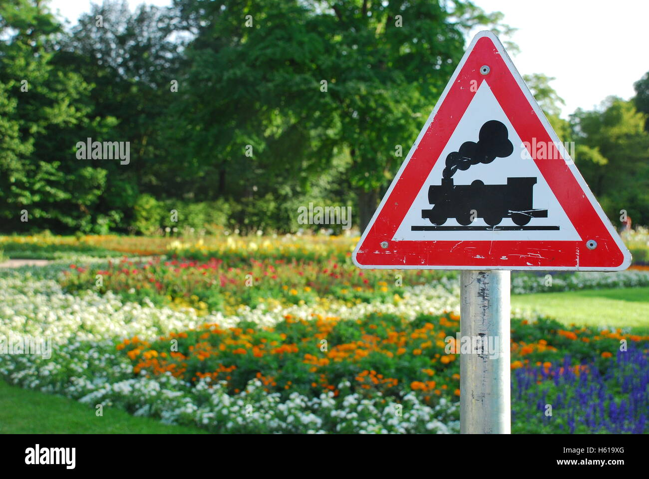 Attention, railway crossing: miniature narrow-gauge railway Hoehenpark Killesberg Stuttgart Baden Wuerttemberg Germany - Stock Image
