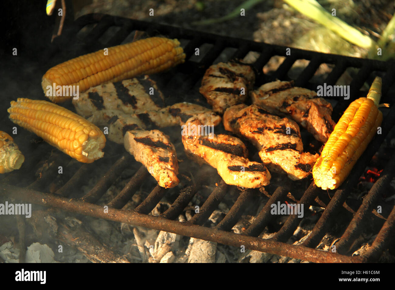 Grilling meat and corn at outdoors camping - Stock Image