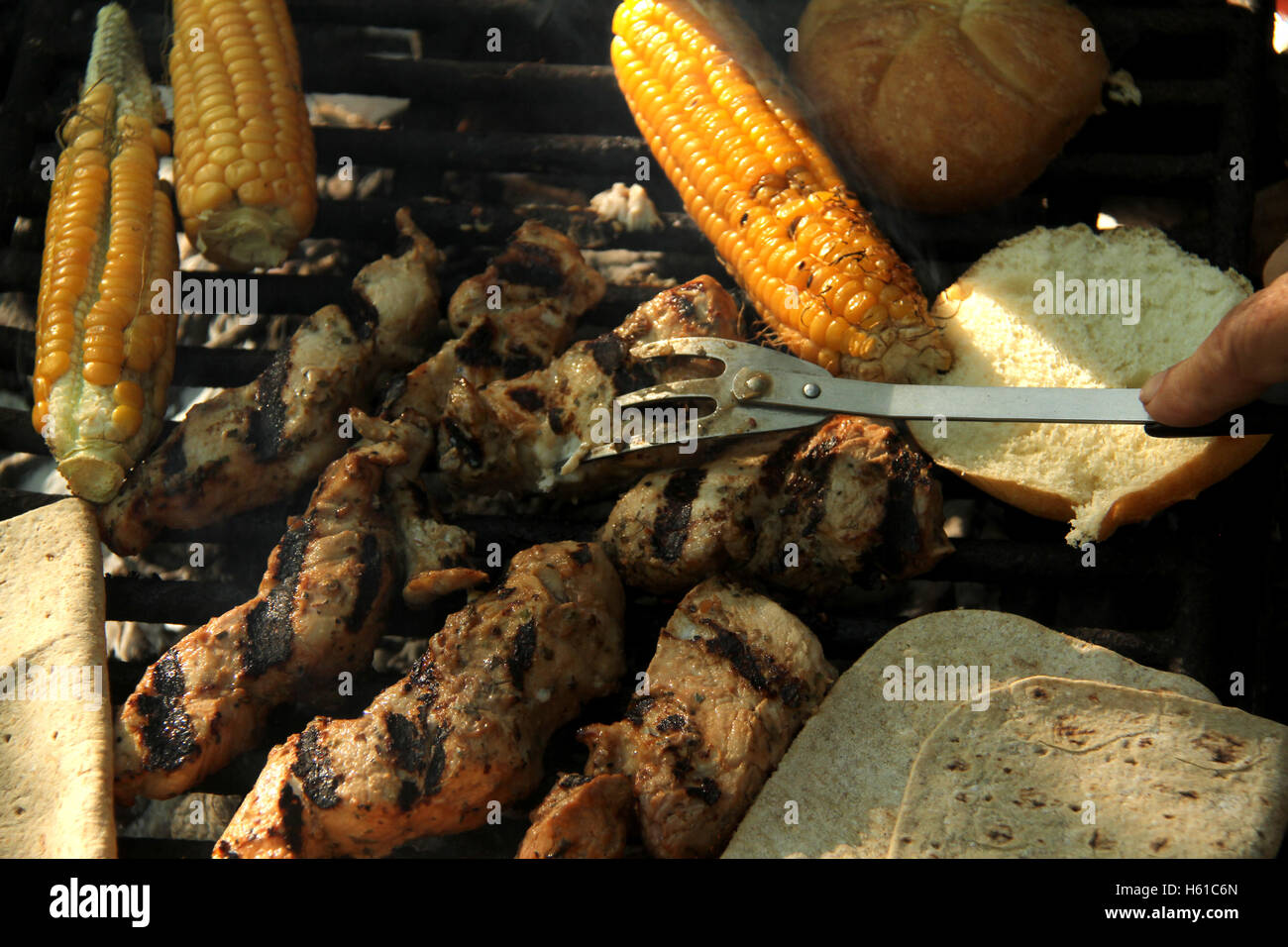 Grilling meat, bread, and corn at outdoors camping - Stock Image