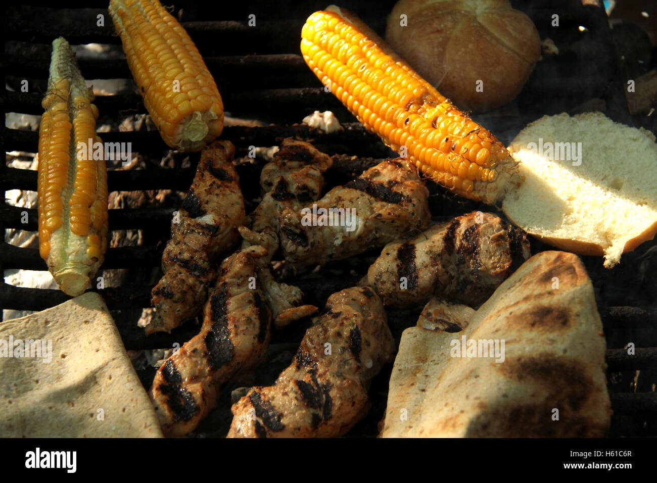 Grilling meat, bread, and corn at outdoor camping - Stock Image