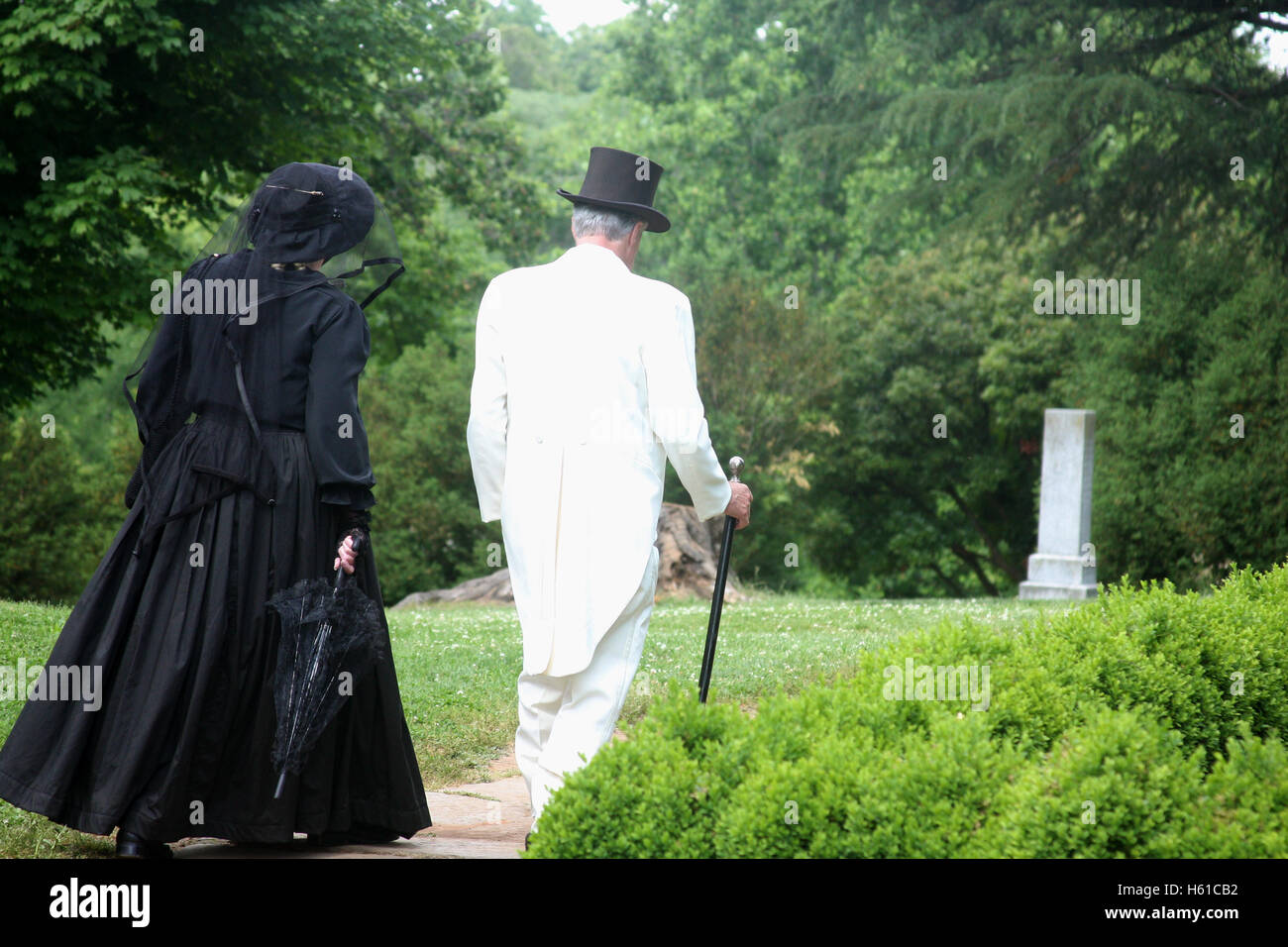 Couple in old style attire walking in park - Stock Image