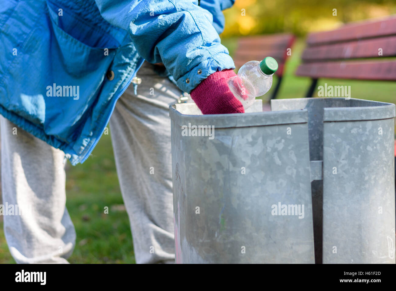 Indigent senior woman scrounging through a bin for bottle on an urban autumn street in a concept of homelessness - Stock Image