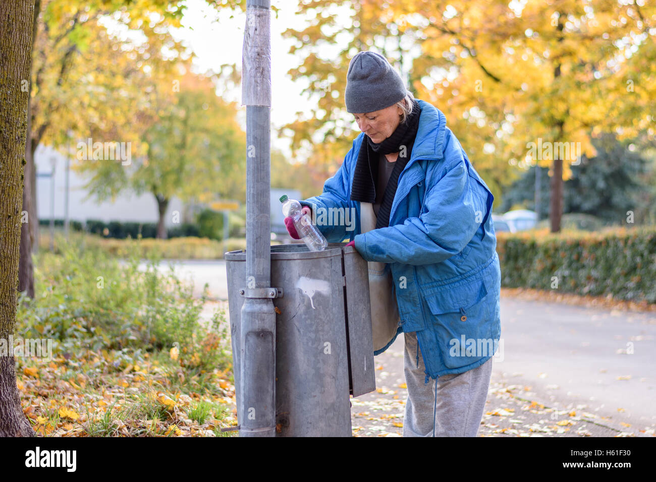 Indigent senior woman scrounging through a bin for food on an urban autumn street in a concept of homelessness and - Stock Image