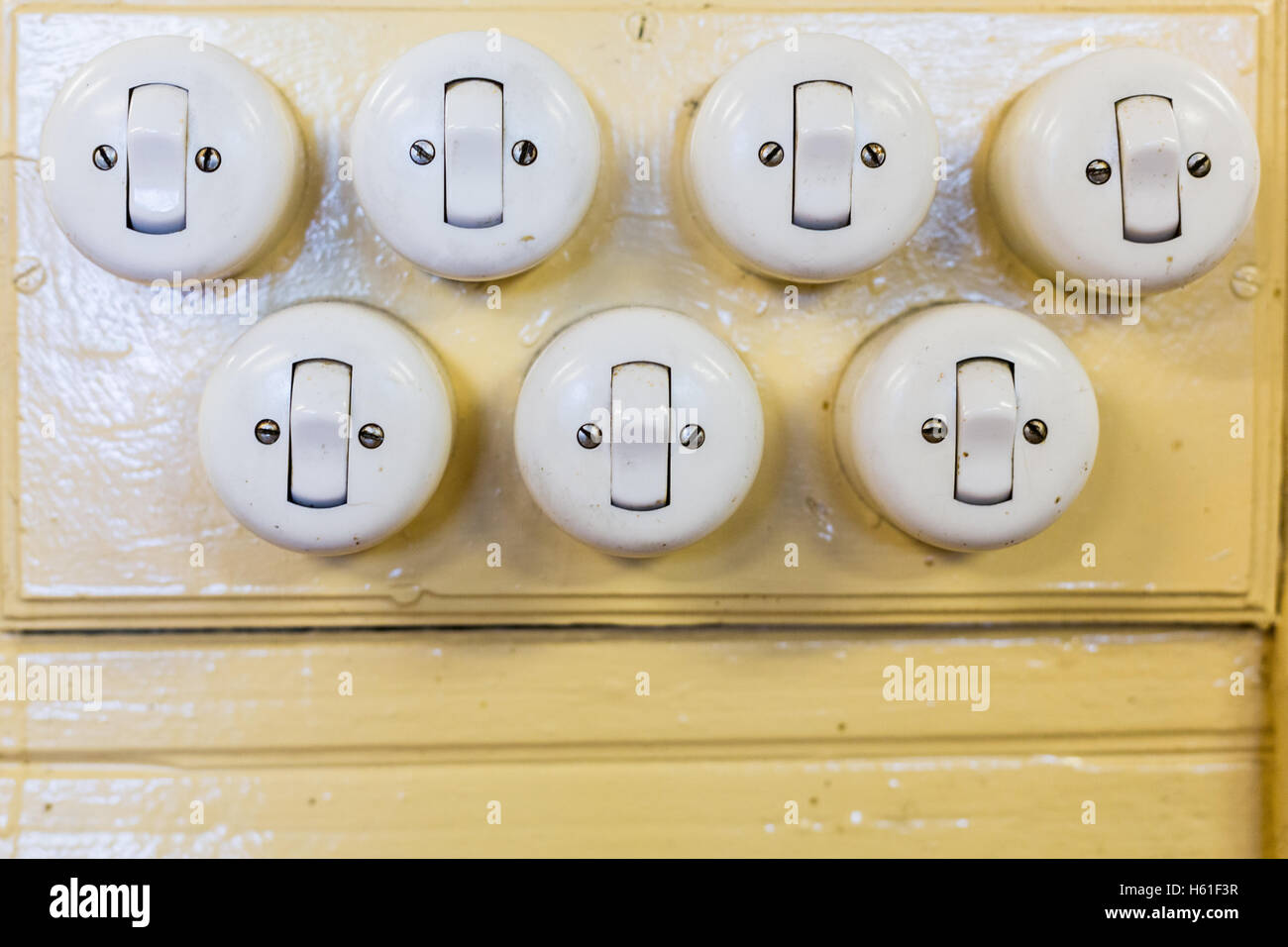 Seven old light switches placed on a wall of an old house. These objects are used to turn off and turn on the light, Stock Photo