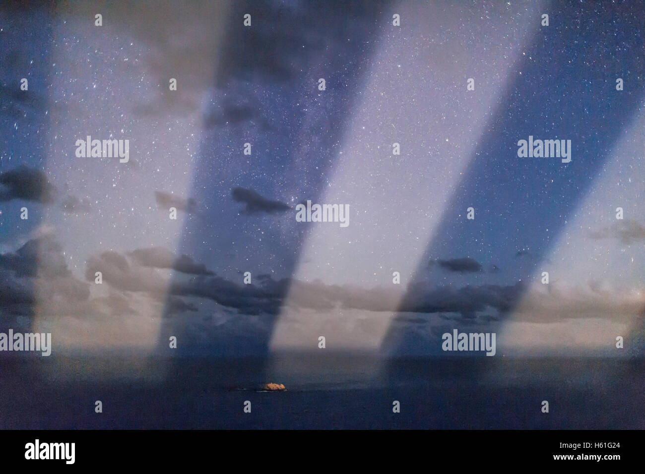 The trio of beams from the Smoky Cape Lighthouse scanning across the sea and sky in an exposure shot as short as - Stock Image