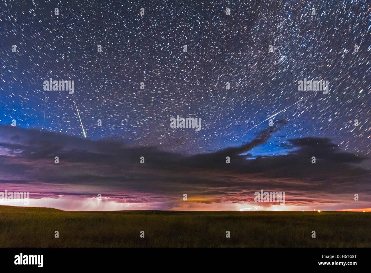 A busy sky – with a line of thunderstorms across the northern horizon, the circumpolar stars trailing above, a bright - Stock Image