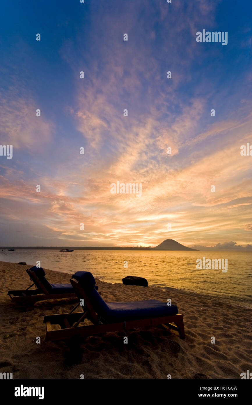 Sunbeds in front of sunset, Siladen island, Sulawesi, Indonesia, Southeast Asia - Stock Image