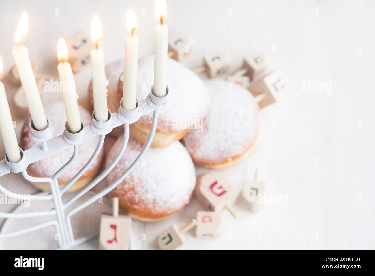 Jewish traditional holiday Hannukah with menorah, doughnuts and dreidles. Copy paste background. - Stock Image