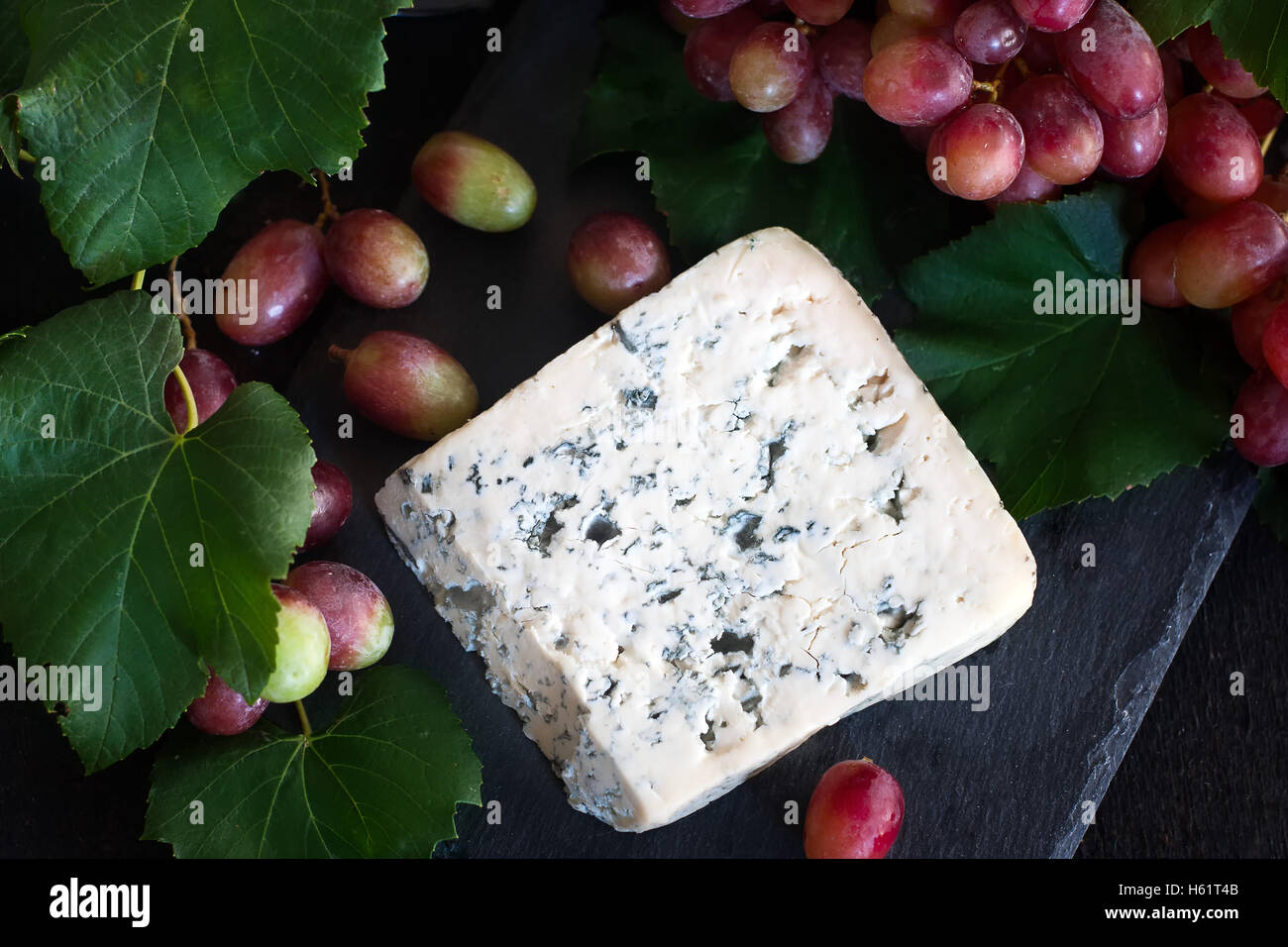 Blue cheese Dorblu with red grape on black background - Stock Image