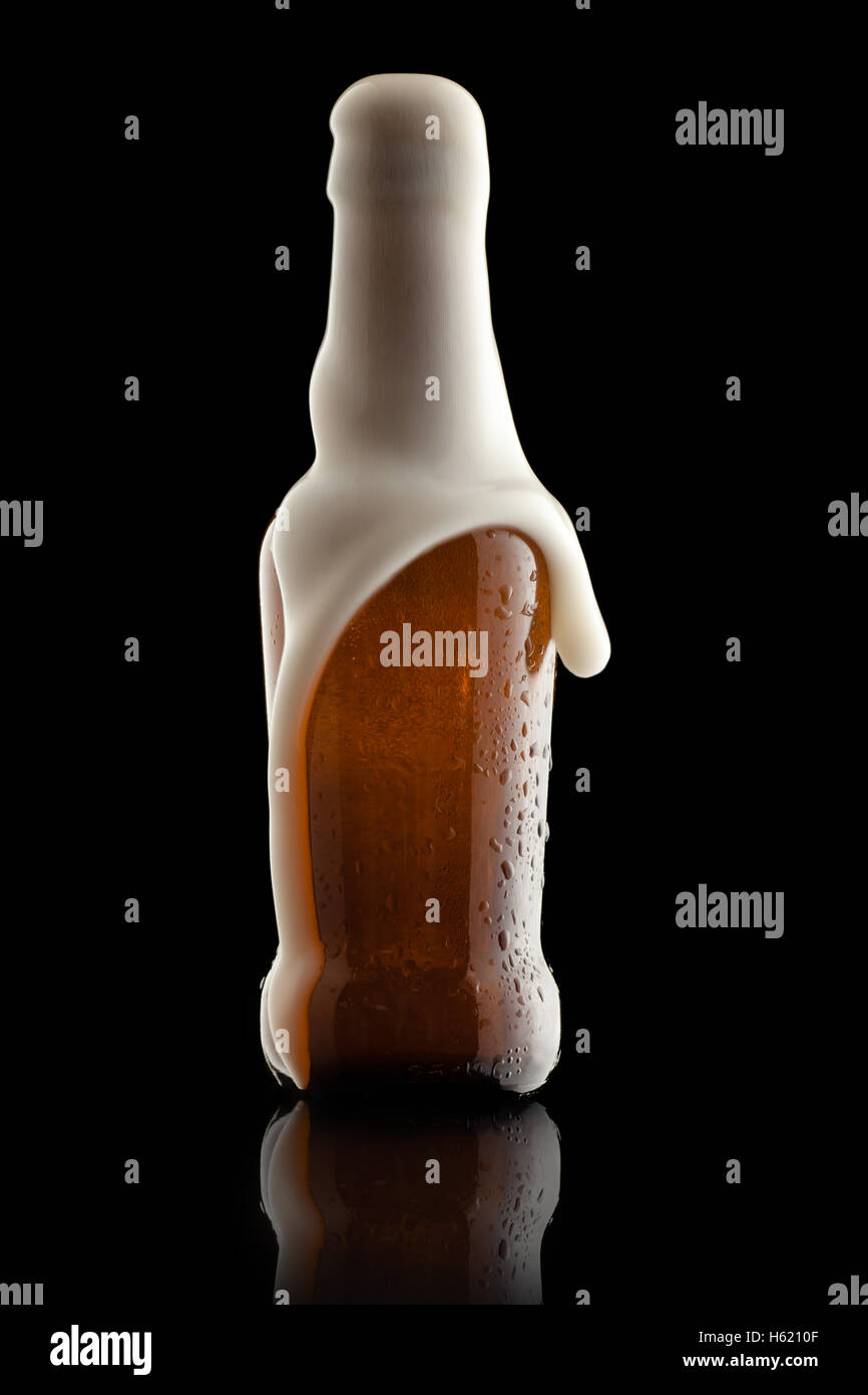 Overflowing Suds Getting Out of a Beer Bottle - Stock Image