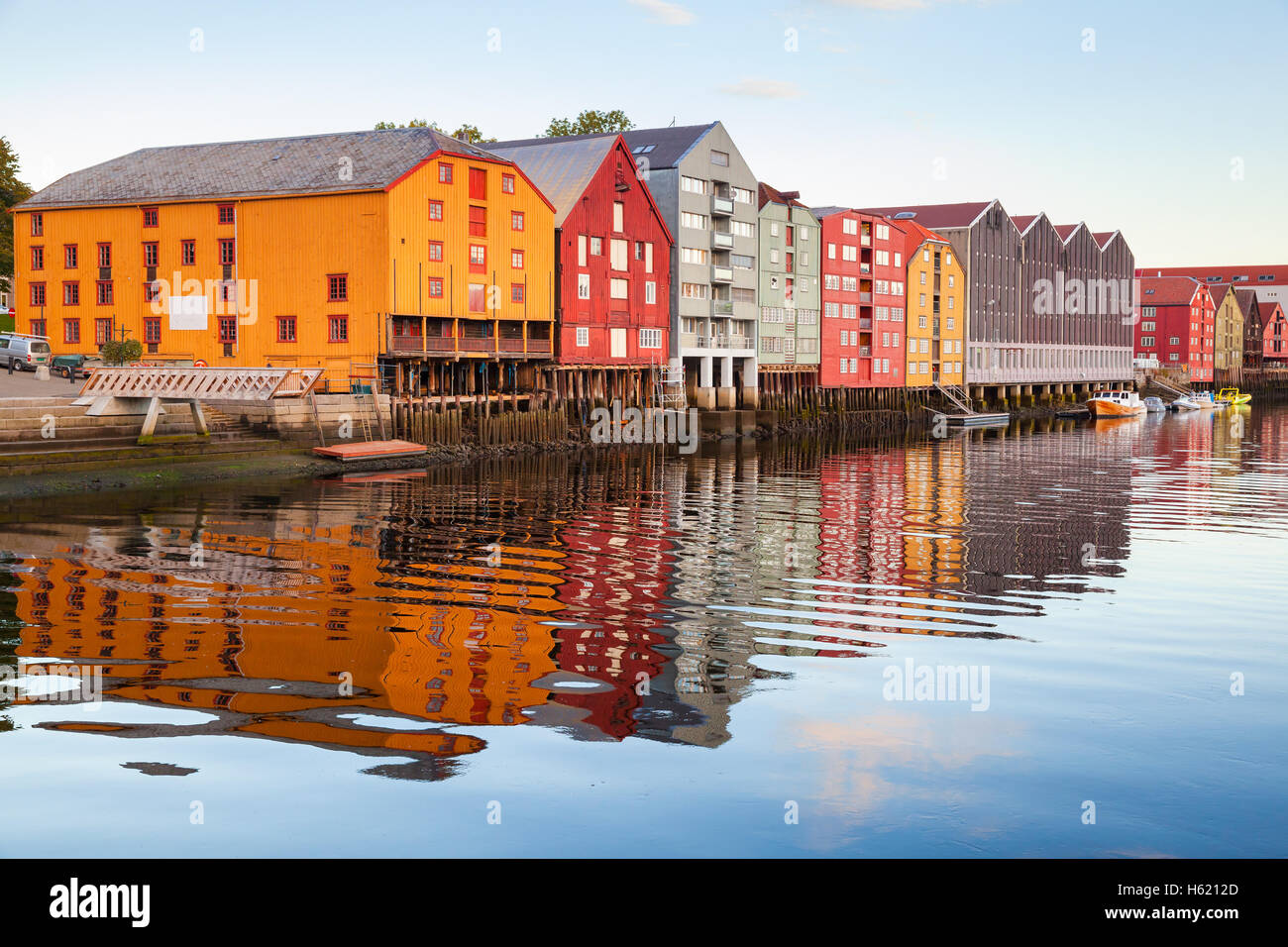 Colorful old wooden houses stand in a row along the river coast. Trondheim, Norway Stock Photo