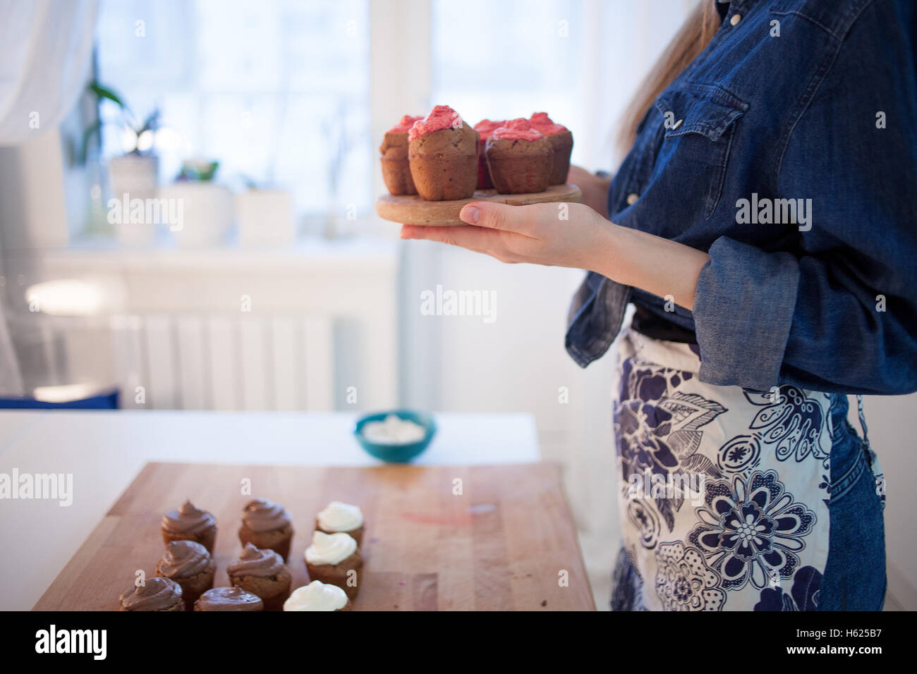 girl holding plate of fresh hot muffins, blurred background - Stock Image