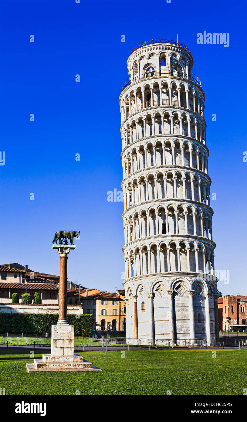 Tall but leaning tower of Pisa in a Miracoli architecture complex with straight wolverine column against blue sky. Stock Photo
