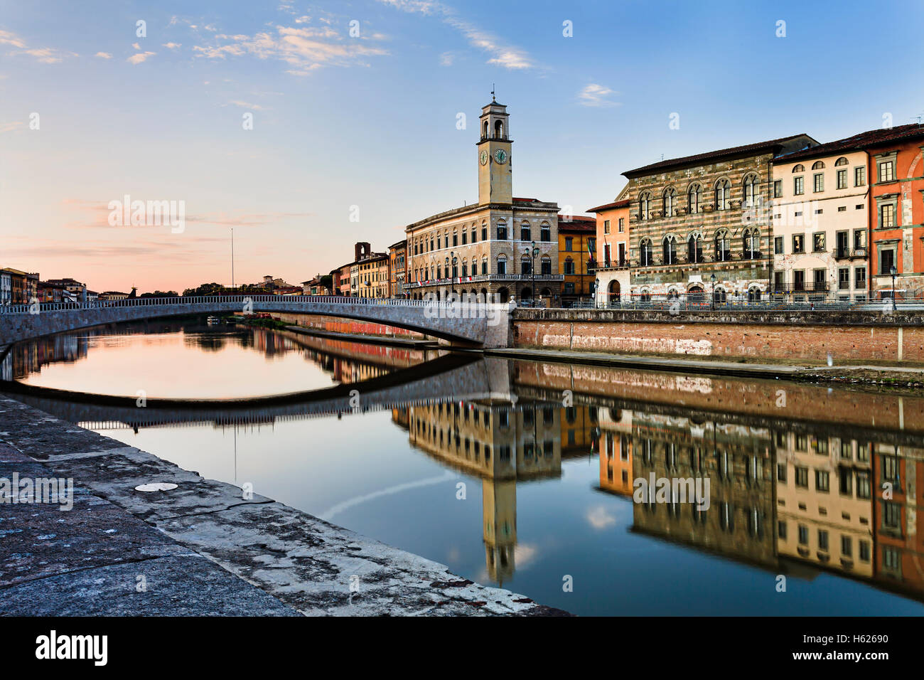 Colourful residential houses along Arno river in the downtown of Pisa - famous historic Italian city. Still waters Stock Photo