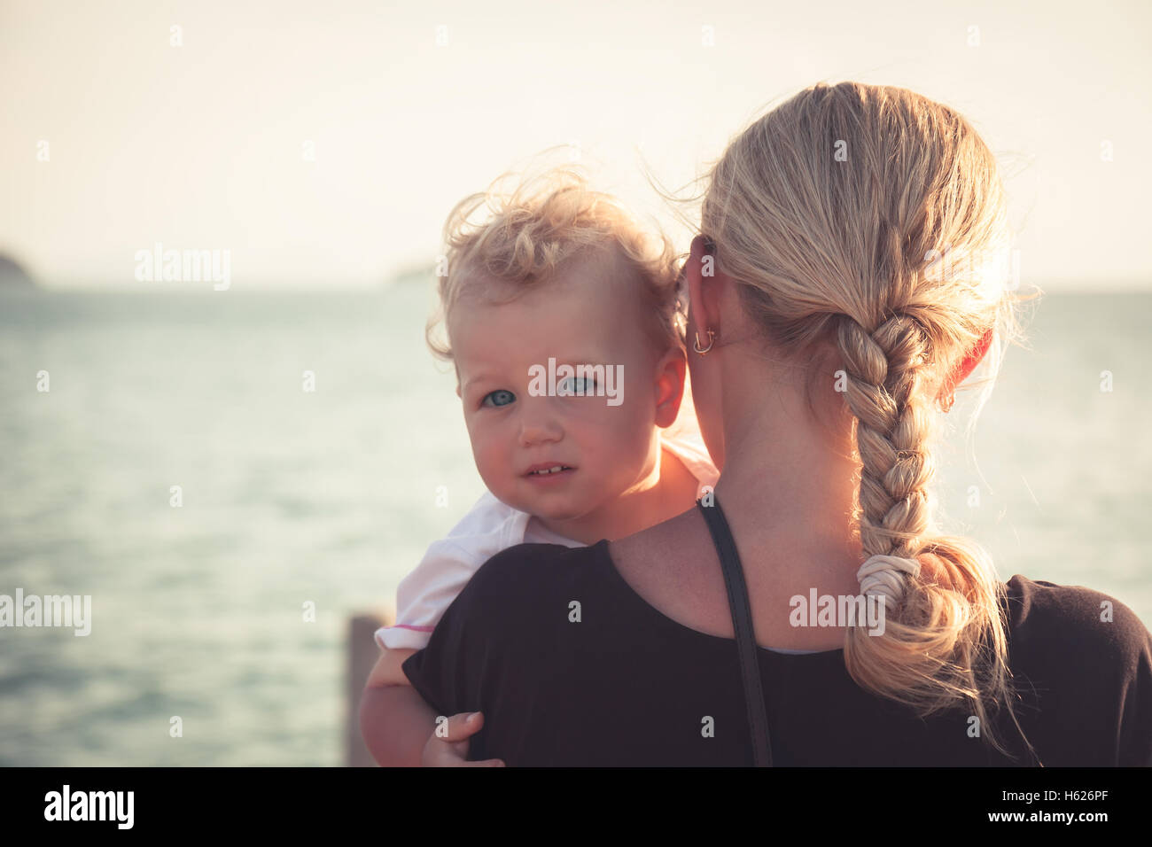 Child with a sincere look hugging his mother sitting on her hands and looking at camera. Mother holding her baby Stock Photo