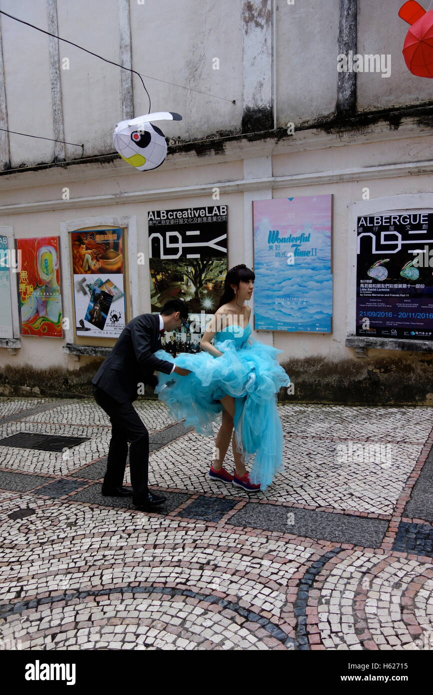 Macau, China couple having wedding photographs taken her dress matches poster on the wall behind her, he is arranging - Stock Image