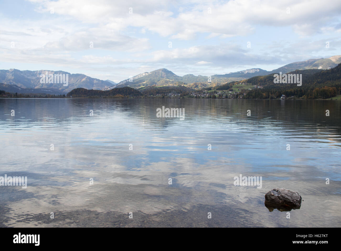 Landscape of the Traunsee Lake in Upper Austria. Water reflections in the foreground with beautiful mountains in - Stock Image