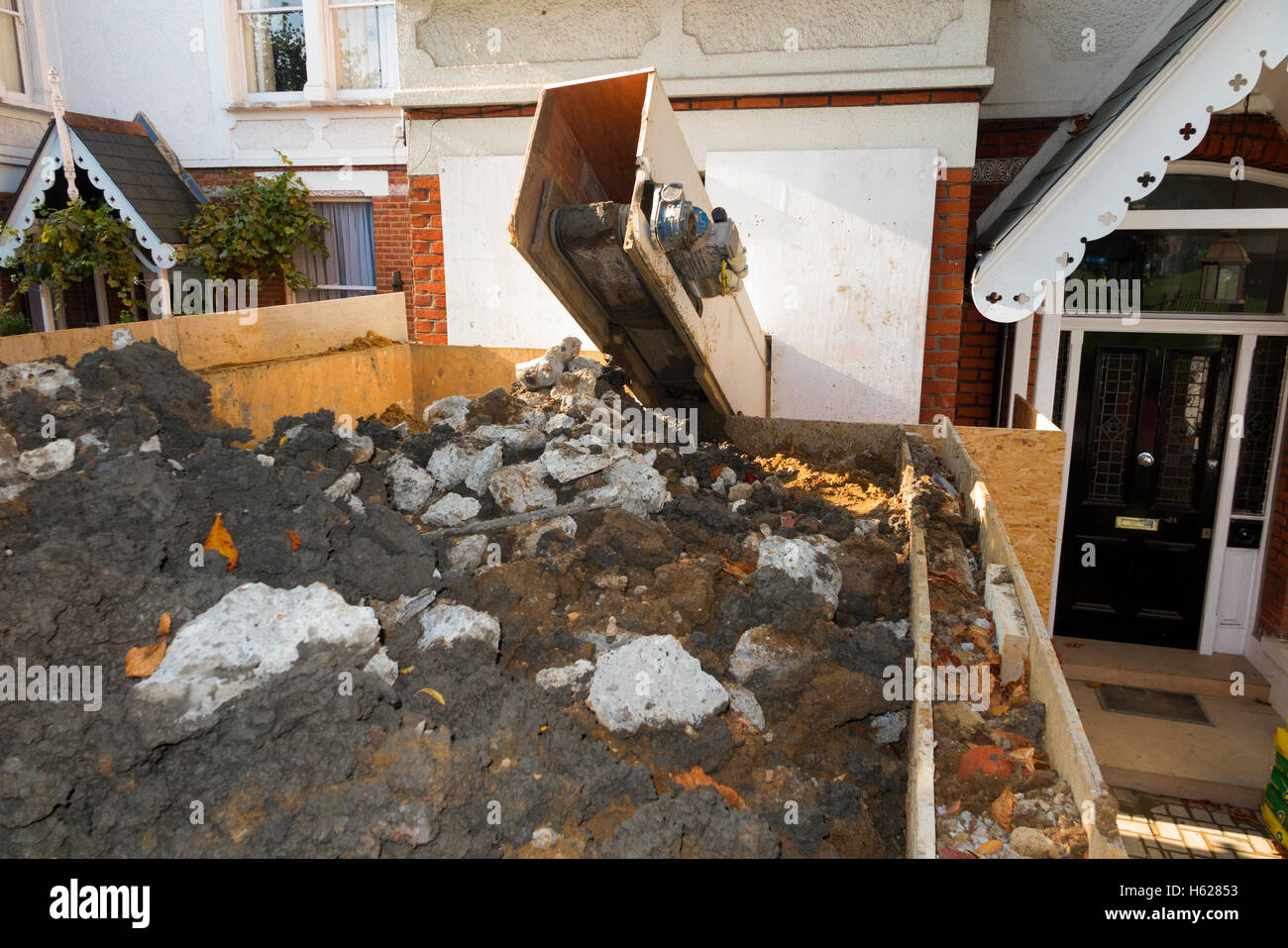 Machine removing soil from basements excavation / excavating the basement / extension / extending property house - Stock Image