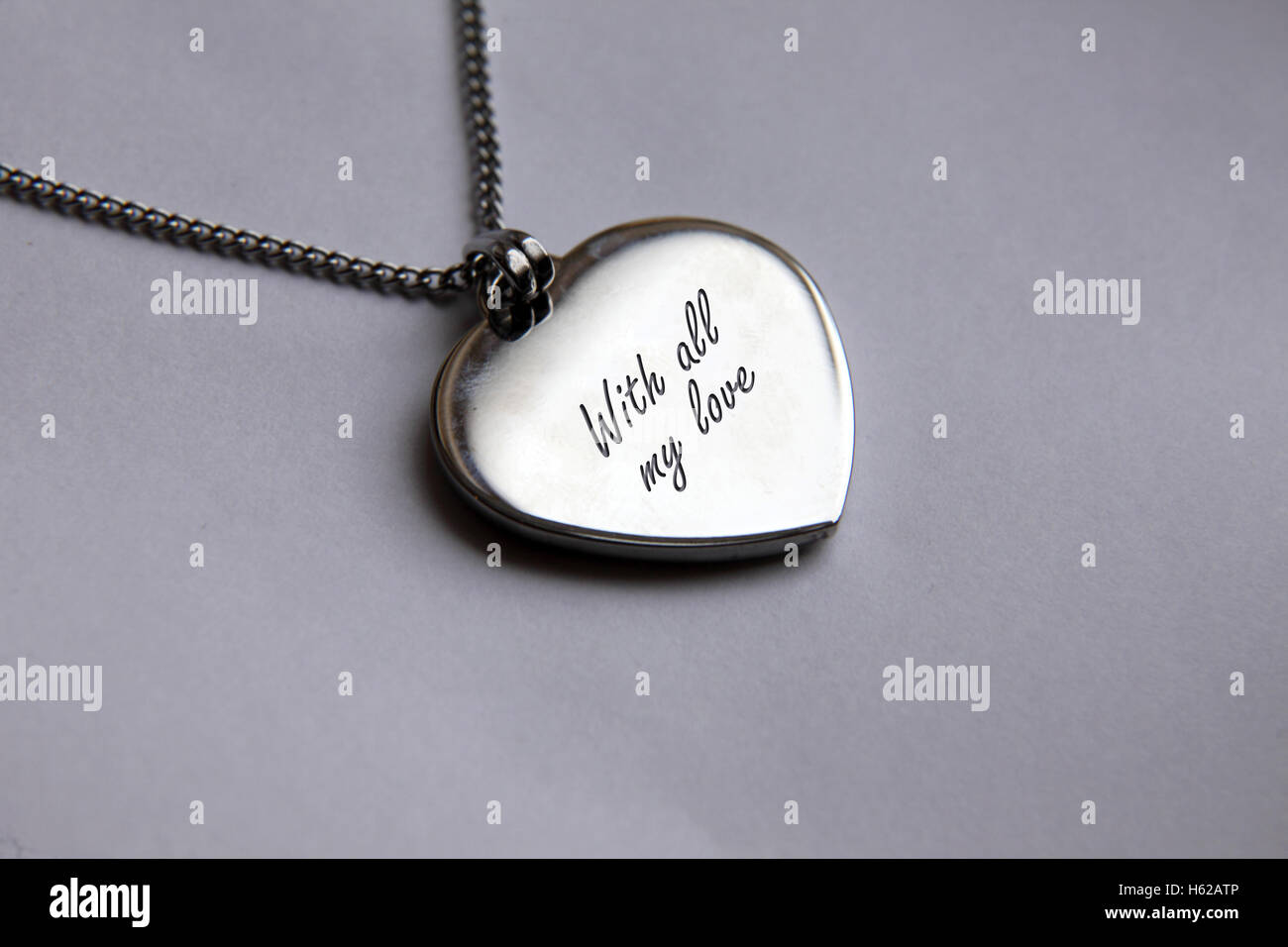 Silver pendant necklace on a small chain engraved 'With all my love' - Stock Image