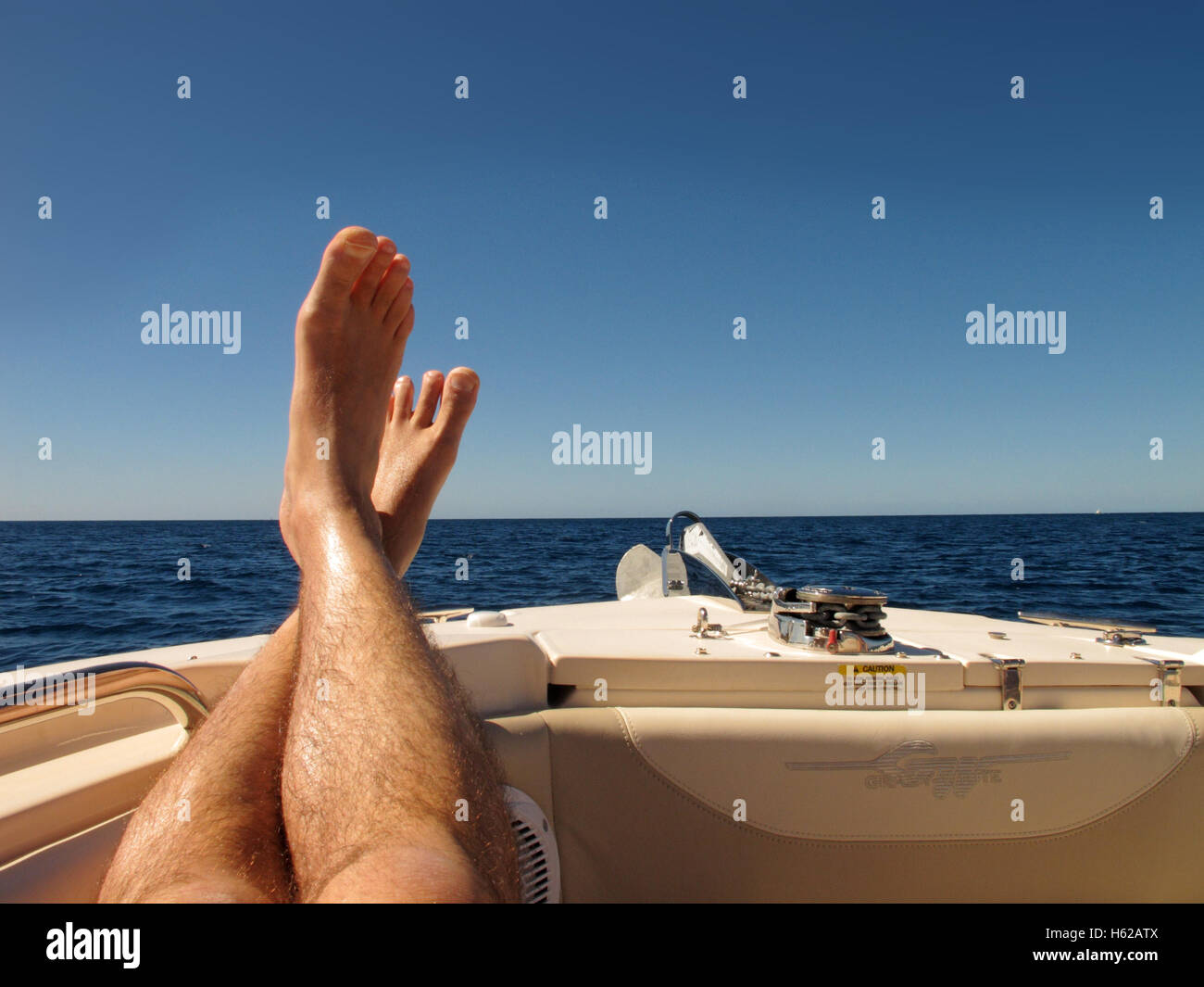 Put your feet up - a pair of feet on the front of a boat with a blue sky behind, on the Caribbean Sea at Barbados - Stock Image