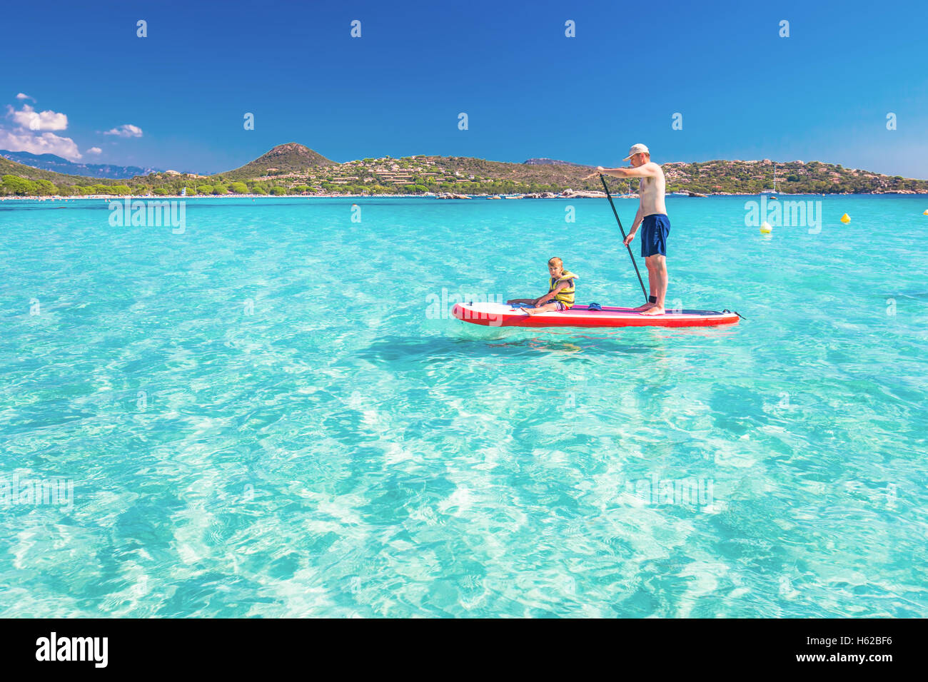 Father with his little happy son having fun on stand up paddle board on Corsica island, France. - Stock Image