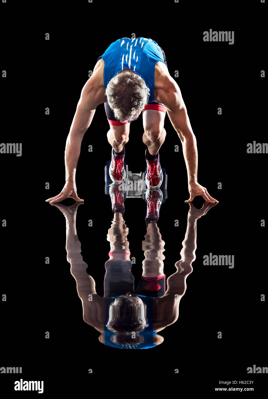 Runner in starting position reflected in water - Stock Image