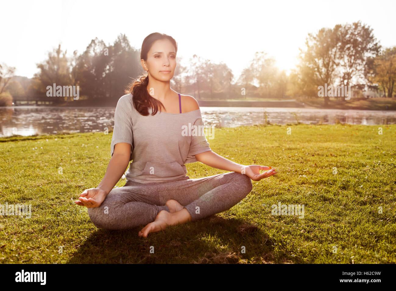 Woman relaxing in Lotus yoga pose - Stock Image