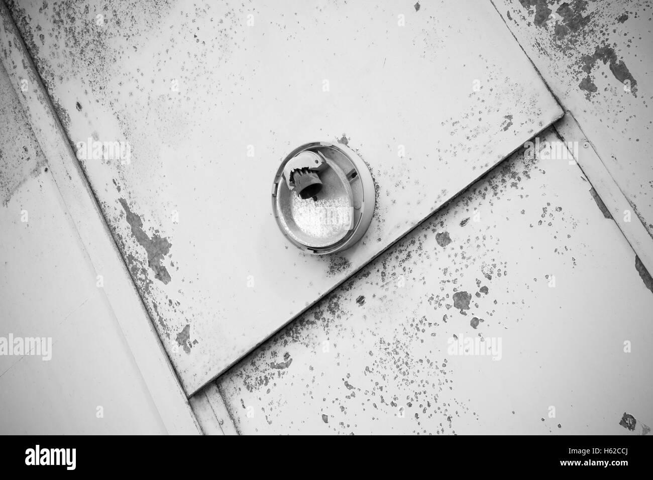 old metallic door with a broken light fixture - Stock Image